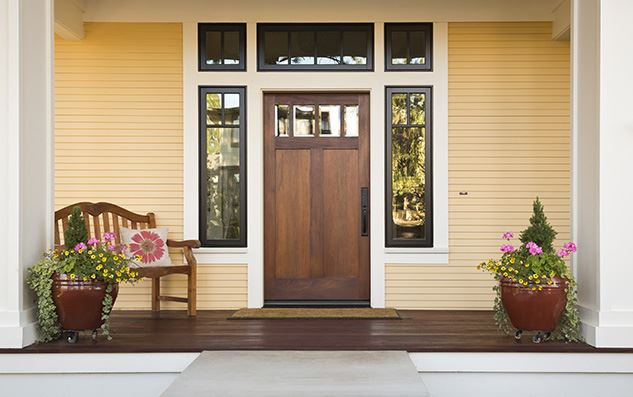 Wooden-front-door-of-a-home-front-view-of-a-wooden-front-door-on-a-yellow-house-with-reflections-in-